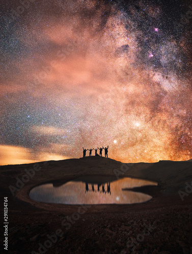 Silhouette of a group of people standing on a mountain. Behind their beautiful starry sky and the Milky Way. Reflection in a small lake. Fototapete