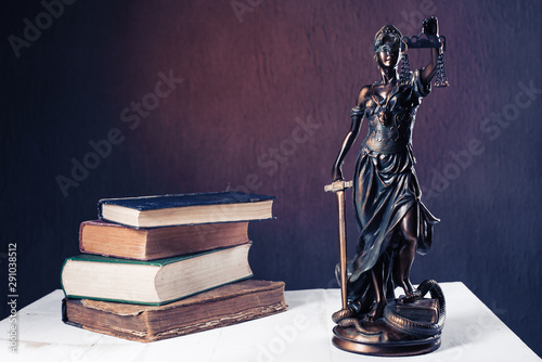 Foto op Plexiglas Historisch geb. Themis figurine stands on a white wooden table next to a stack of old books.