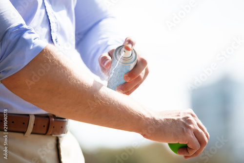 Photographie Man Spraying Anti Insect Deet Spray On His Arm