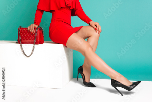 Fotografie, Obraz  Sexy woman in high heels with red handbag on a blue background.
