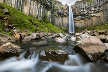 Wide Angle Icelandic Landscape With A Large Waterfall Surrounded By Basaltic Rocks And Green Vegetation