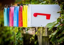 Close Up Of A Row Of Colorful Traditional American Letterboxes Surrounded By Ivy, Against A Green Bokeh Background