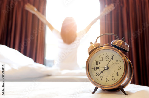 Obraz Morning of a new day, alarm clock wake up man sitting in the room. A man stretch the muscles at window. Health and care concepts - fototapety do salonu