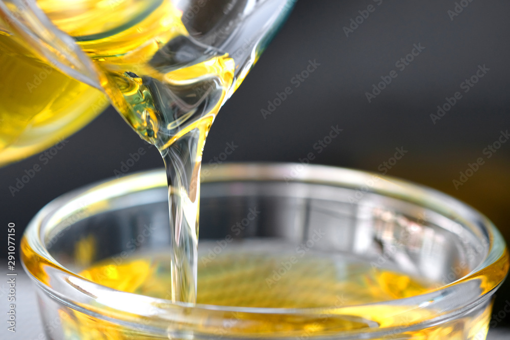 Fototapeta Pouring olive oil in the a glass bowl at stone kitchen. Prepare for cooking concept. Healthcare and Beauty Concept.