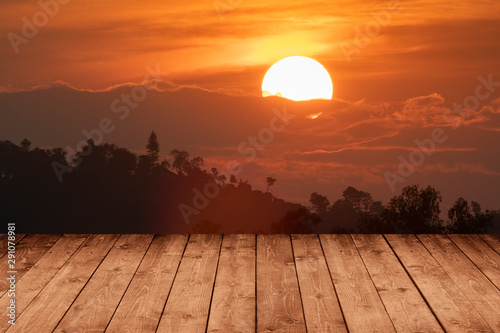 Foto auf Leinwand Rotglühen wood plank with abstract silhouette natural big sunset over pine tree mountain background for product display.