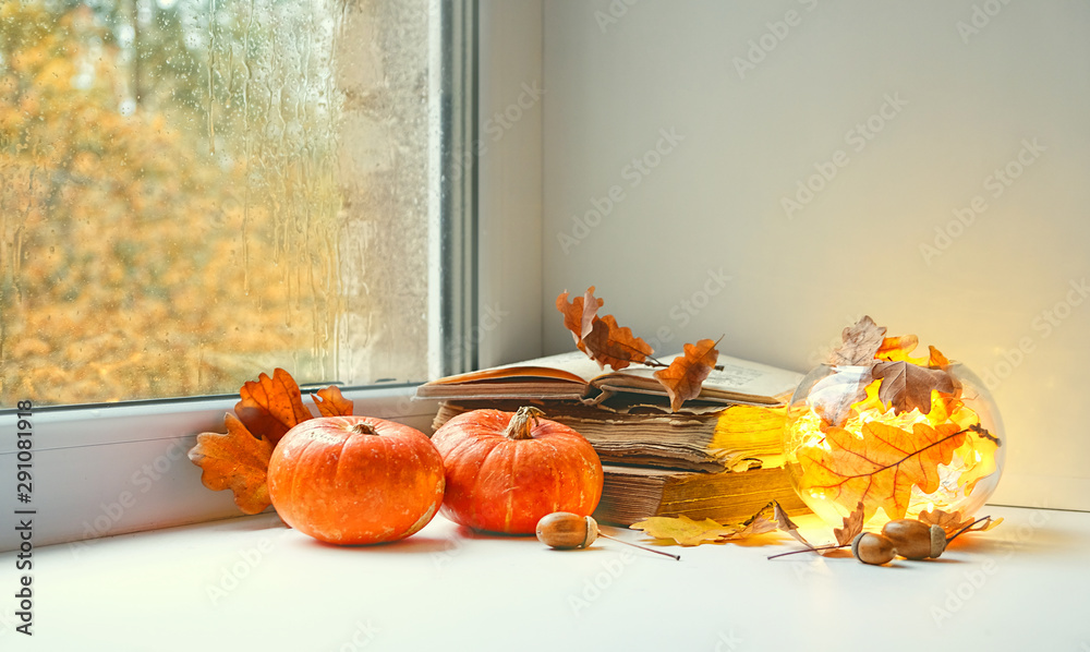Fototapety, obrazy: orange pumpkins, books and candle lantern on window sill. beautiful autumn seasonal composition. fall time, thanksgiving and halloween concept. home comfort. copy space