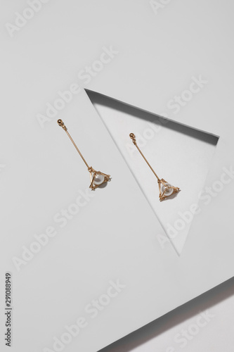 Closeup shot of earrings with pearl beads made of shiny golden metal in the form of geometric shapes Wallpaper Mural