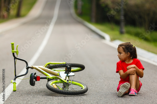 The little girl fell off the bike on the road Canvas-taulu