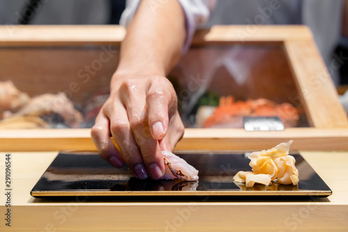 Fotografía Japanese Sushi Chef serve sushi by hand on the black shimmer plate