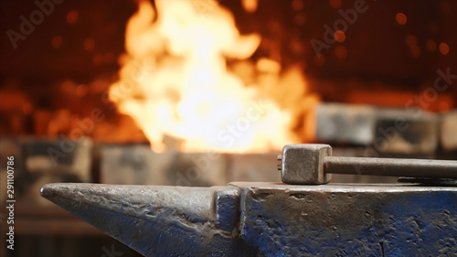 Photo Hammer on anvil in forge on furnace with fire background in smithy workshop