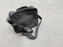 Black Business Satchel Bag Left Behind On The Concrete Floor, Man Fashion Accessories For Carrying An Laptop Or Documents During Business Trip In Urban Area Concept