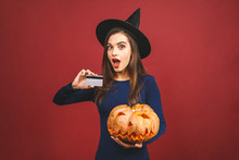October Sale! Halloween Witch With A Carved Pumpkin And Credit Card - Isolated On Red Background. Emotional Young Woman In Halloween Costume. Halloween Party Girl.
