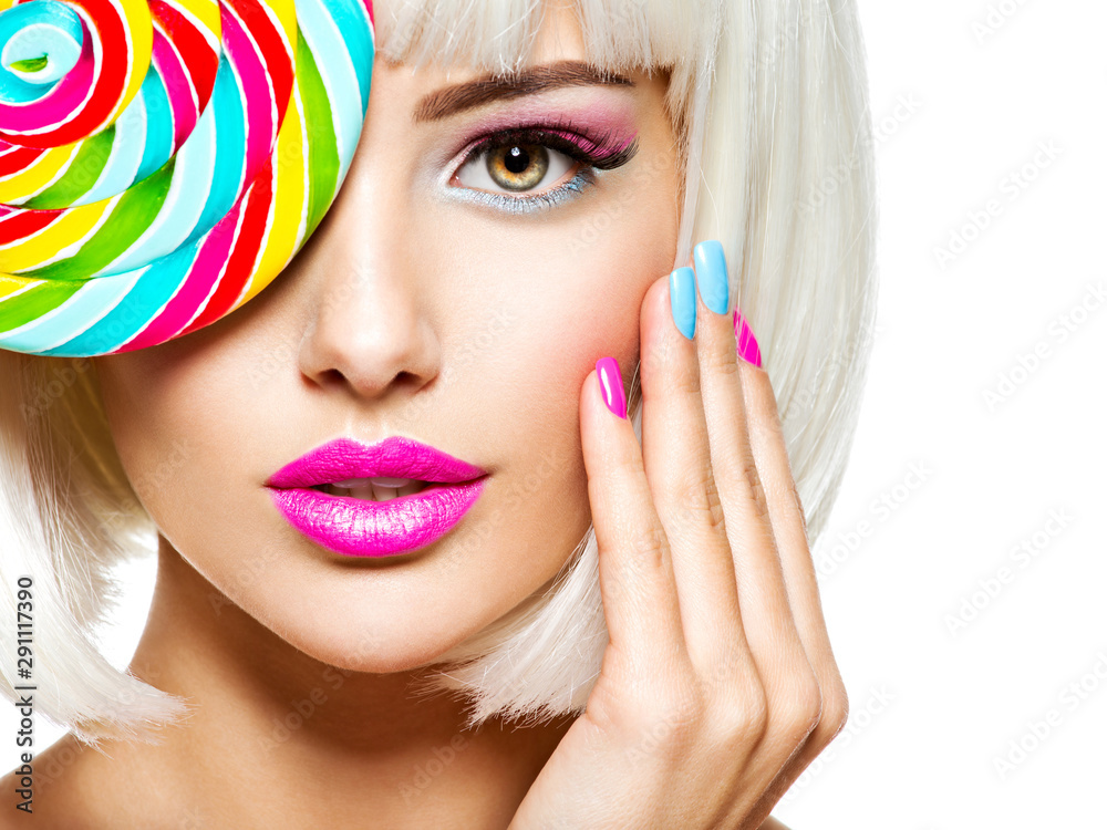 Fototapeta Face of a beautiful  girl with pink eye make-up and multicolor nails. Sweet candy.
