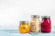 Leinwanddruck Bild - Fermented vegetables in jars. Sauerkraut, pickled beets and pickled squash on a light wooden background. Traditional Russian pickles. Copy space