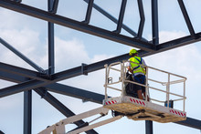 Professional Installation Work On A Construction Building Site. Assemblers Perform High-altitude Installation Works On The Telescopic  Boom Lifts Platforms. Installation Of Huge Steel Beams.