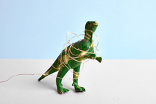 Funny Green Tyrannosaur Rex In Red Santa Hat And Christmas Light. Blue Minimal Concept