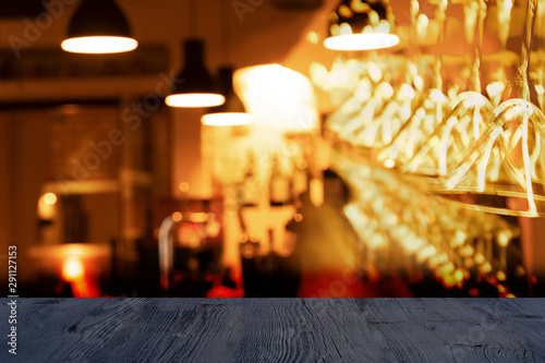 Αφίσα  top of black wood table with blur alcohol drinking glass and lamp hanging in bar
