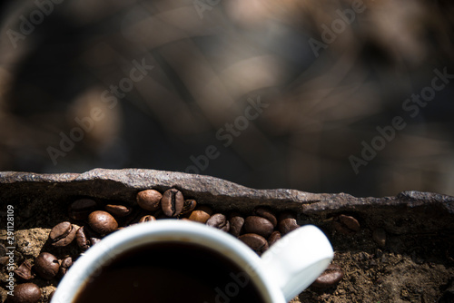 Cup of coffee and coffee beans closeup on earth and iron background
