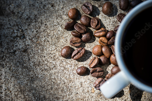 Cup of coffee and coffee beans on a stone background