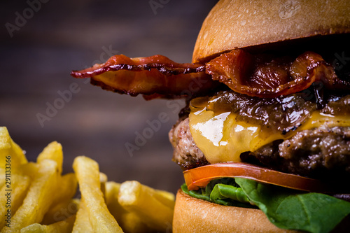 Fototapeta Craft beef burger with cheese, bacon, rocket leafs, caramelize onion and french fries on wood table and rustic background. obraz