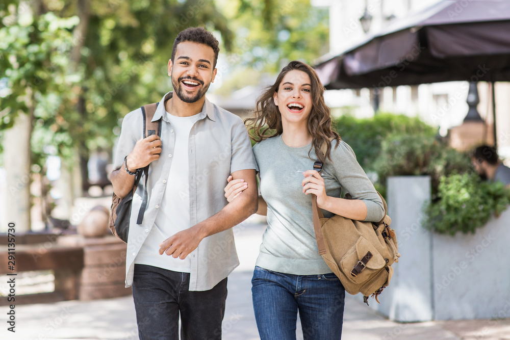 Fototapety, obrazy: Beautiful happy couple summer portrait. Young joyful smiling woman and man in a city.  Love, travel, tourism, students concept