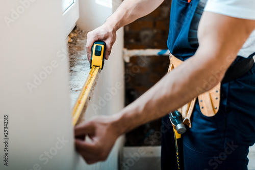 Obraz cropped view of handyman measuring wall with yellow measuring tape - fototapety do salonu