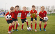 Leinwanddruck Bild - Happy Junior Sports Team. Young Boys in Soccer Team Holding Golden Cup and Soccer Balls. Group of children Winning School Sports Tournament. Schools Football Championship for Kids