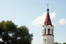 Close-up Of Maroon Top Of Orthodox Church Bell Tower With Cross Against Sky And Trees