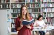 canvas print picture - Young pretty woman with book in library