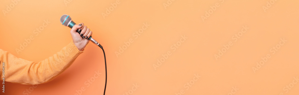 Fototapety, obrazy: hand holding microphone over orange background, panoramic mock up image