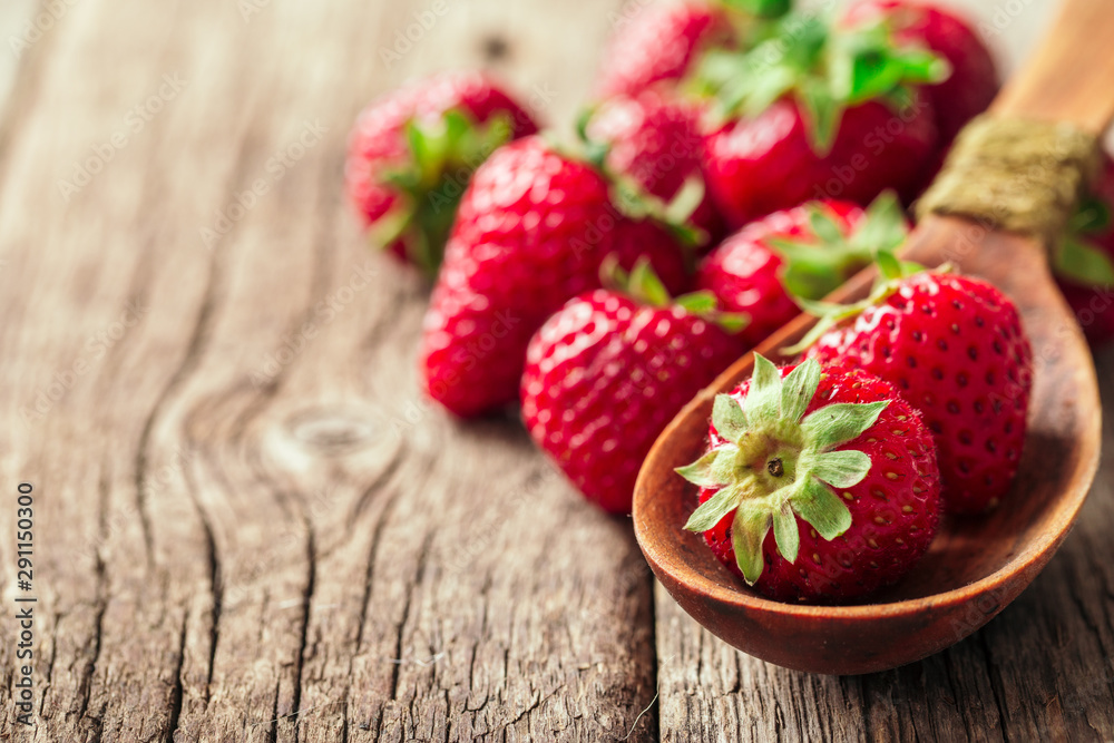 Fototapety, obrazy: Freshly picked Strawberry in spoon on wooden background. Healthy eating and nutrition.