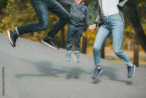 Joyful happy family jump on country road in autumn. Closeup. Canvas Print