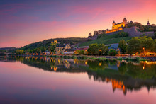 Wurzburg, Germany. Cityscape Image Of Wurzburg With Marienberg Fortress And Reflection Of The City In Main Rive During Beautiful Sunset.