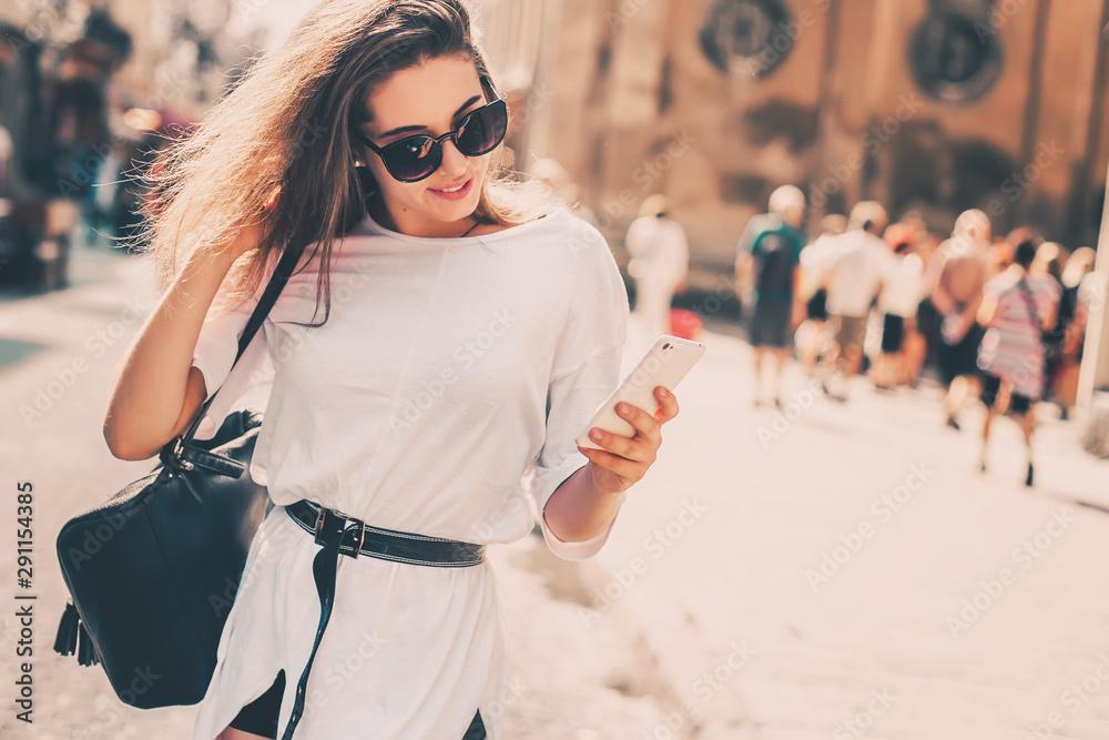 Fototapeta Beautiful woman traveler  using phone walking on the old town street.