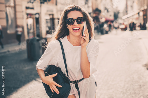 obraz PCV Young stylish woman using phone walking on the street, wearing trendy outfit.