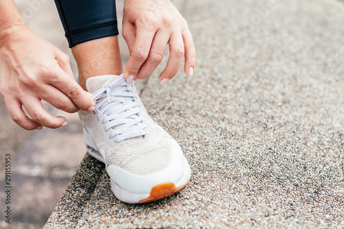 Photographie  Close up shot of sportswoman's hands tying shoelaces