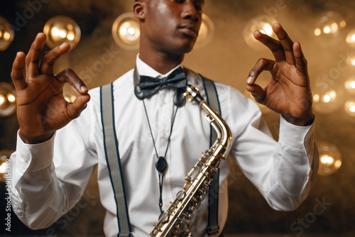 Black jazz performer with saxophone shows OK sign - 291158389