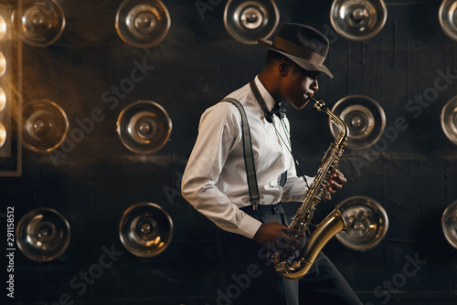 Black jazzman in hat plays the saxophone on stage - 291158512