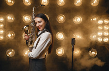 Female Saxophonist Poses With ...