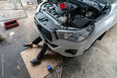DIY. Mechanic lying and working under car at home garage - Engine oil change,