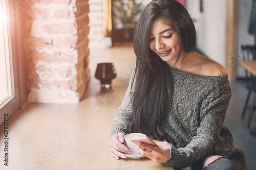 Beautiful girl uses a phone and drinks coffee, sitting in a cozy cafe. - 291165792