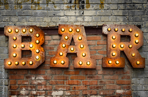 Obrazy z napisami  inscription-from-large-metal-letters-decorated-with-glowing-light-bulbs-on-the-brick-wall