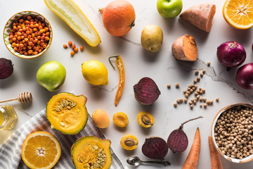 top view of season autumn vegetables, fruits and berries with chickpea on marble surface