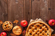 canvas print picture - Homemade autumn apple pie bottom border. Above view table scene over a rustic wood background with copy space.