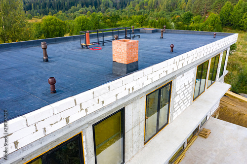 Obraz Roof waterproofing. Building construction. A protective layer was applied on the roof of the house. Installation of a waterproofing layer. Construction works. Bitumen insulating layer. - fototapety do salonu