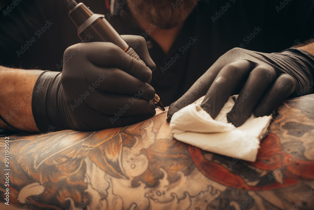 Fototapeta Close up tattoo machine. Tattooing. Man creating picture on his back by a professional tattoo artist.
