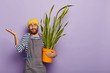 Leinwanddruck Bild - Potted flowering concept. Confused young man florist grows house plant, raises palms with hesitation, thinks how to fertilize sansevieria, wears uniform, isolated over purple wall, hand tool in pocket