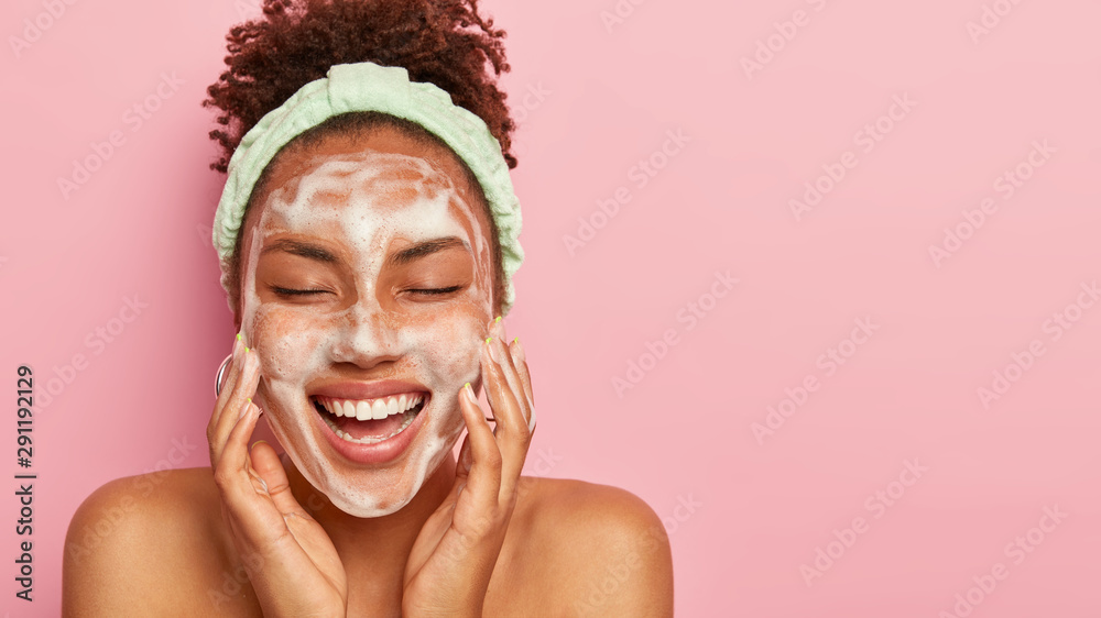 Fototapeta Beautiful dark skinned young lady cleans and washes face with foam, massages cheeks, closes eyes from pleasure, enjoys hygiene treatment, stands alone against pink background. Skin care concept