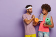 Leinwanddruck Bild - Horizontal shot of serious mixed race woman and man hold hands together, meet in gym, have training together, carry fitness mats, wear soft towels on shoulders, isolated on purple background