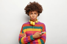 Upset Curly Afro Woman With Sad Look, Uses Mobile Phone, Cannot Withdraw Money From Online Account, Uses Headphones For Listening Music, Wears Casual Striped Jumper, Poses On White Background